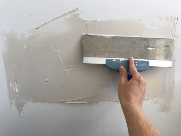 applying drywall mud on a concrete wall